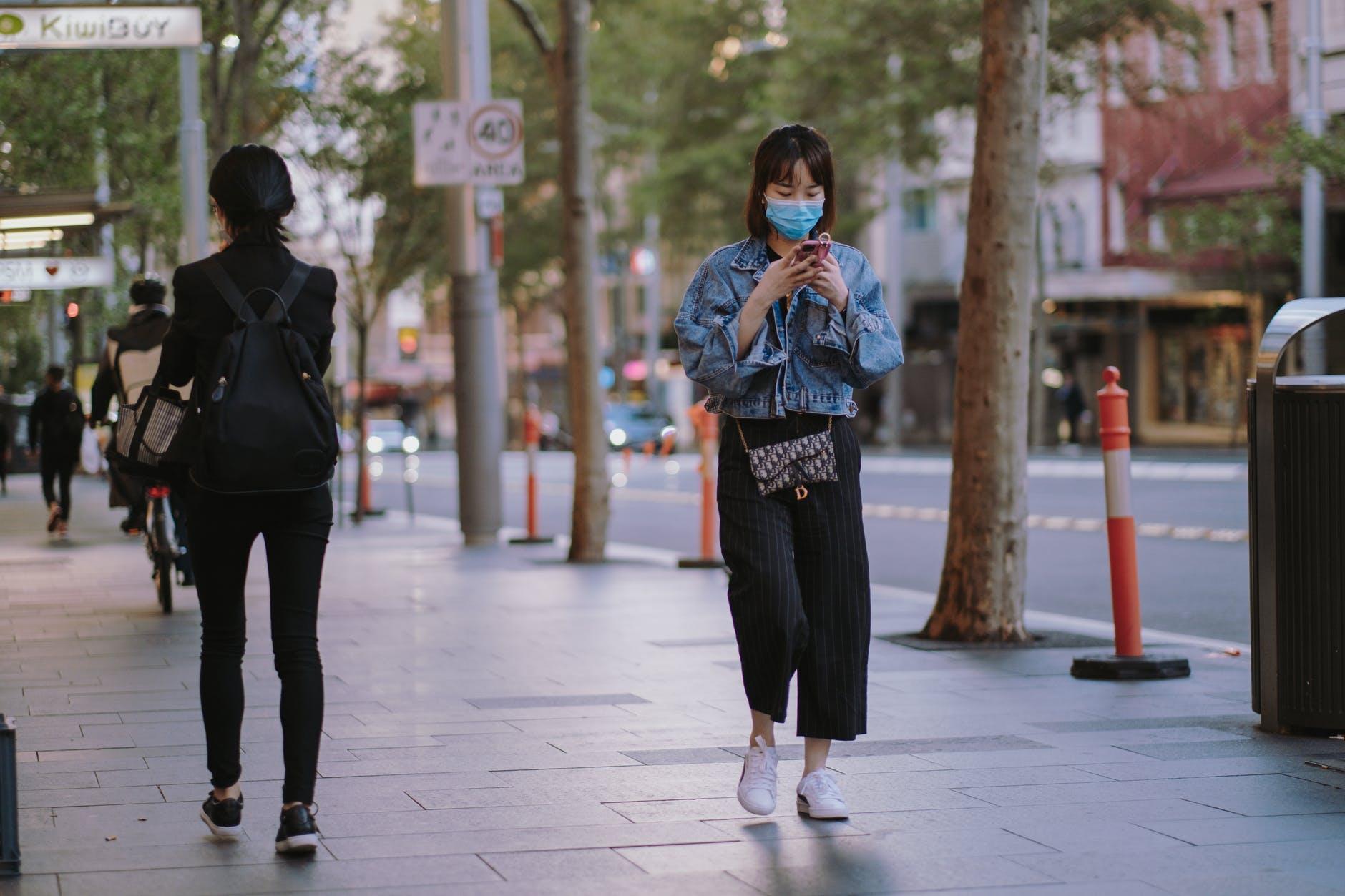 woman in denim jacket and black pants walking on sidewalk